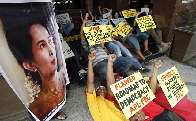 Filipino activists stage a die-in while chanting slogans as they display a poster of Myanmar's pro-democracy leader Aung San Suu Kyi, during a rally outside Myanmar embassy in Manila