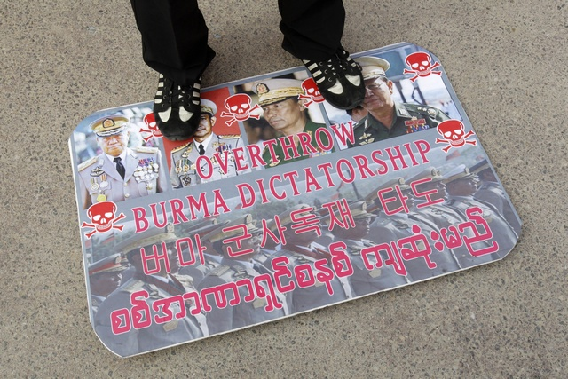 Activist stands on placard with portraits of Myanmar's military government leaders during rally in front of the Myanmar embassy in Seoul
