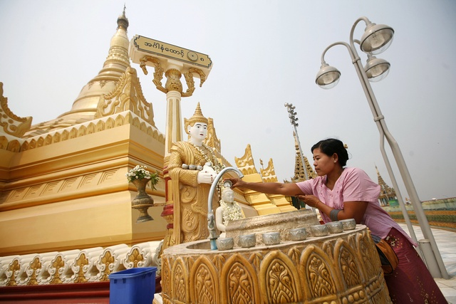 A woman washes a statue of Buddha at the Uppatasanti Pagoda in Myanmar's new capital of Naypyitaw