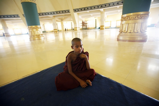 A novice Buddhist monk sits in the Uppatasanti Pagoda in Myanmar's new capital of Naypyitaw