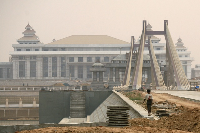 A worker walks in front of the new parliament building under construction in Myanmar's new capital of Naypyitaw