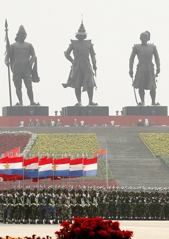 Soldiers carry their weapons and flags as they march during the Armed Forces Day parade in Myanmar's capital Naypyidaw