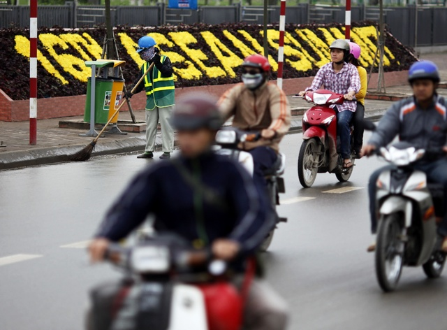 Vietnamese people ride their motorcycles past the venue for the 16th ASEAN Summit in Hanoi