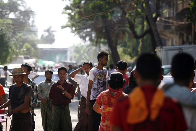 People react as they gather at the site of the explosions in Yangon