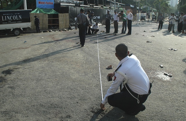 Policeman investigates the site in which three bombs exploded in front of the X20 water pavilion, during Thingyan, Myanmar's new year festival in central Yangon