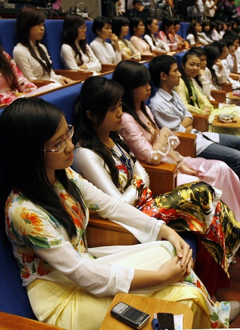 Vietnamese students, in traditional 'ao dai' dress, attend the opening ceremony of the 16th ASEAN Summit in Hanoi