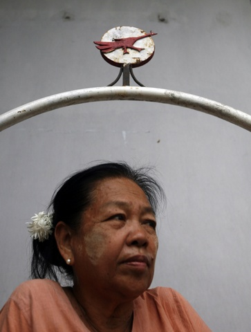 Woman sits under an iron fighting peacock sculpture, used in the NLD's campaign in the 1990 general election, in Yangon