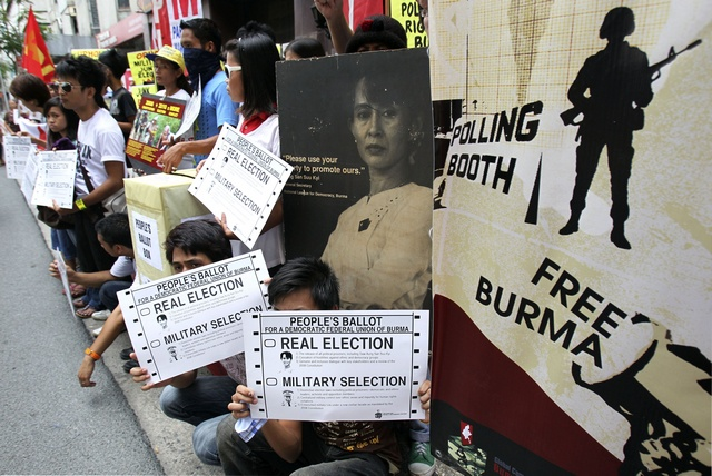 Solidarity activists from the Free Burma Coalition Philippines display signs during a protest in front of the Myanmar embassy in Makati city