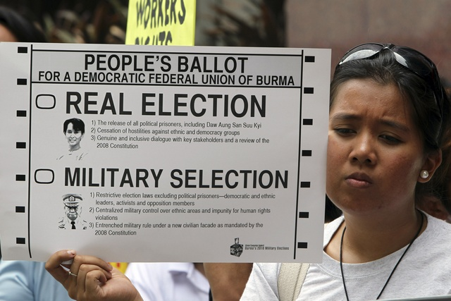Solidarity activist from the Free Burma Coalition Philippines holds up a poster during a protest in front of the Myanmar embassy in Makati city