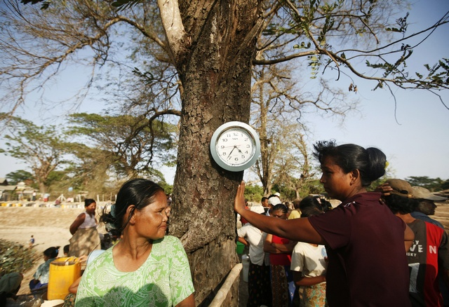 Clock hanging on tree is seen as people line up to collect water at lake in Dala township