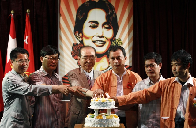 Activists from Myanmar and South Korea pose for photographs in front of a portrait of Aung San Suu Kyi during an event celebrating her birthday in Bucheon