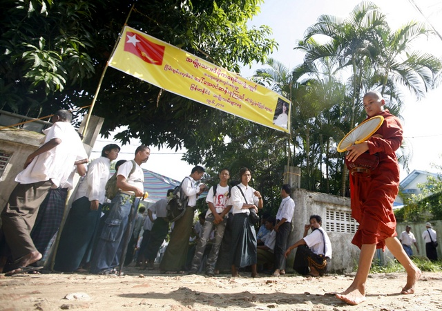 A Buddhist monk walks in front of a house belonging to a member of Myanmar's NLD as fellow members celebrate the 65th birthday of Myanmar's pro-democracy leader Aung San Suu Kyi, in Yangon