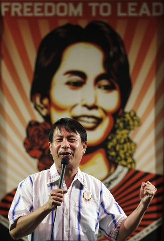 A Burmese activist sings a song in front of a portrait of Aung San Suu Kyi during an event celebrating her birthday in Bucheon