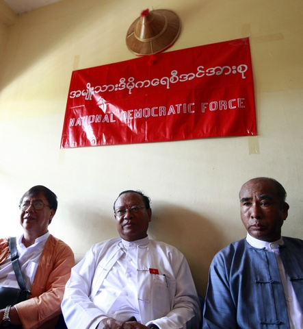 Members of the National Democratic Force party sit inside their party's new headquarters in Yangon