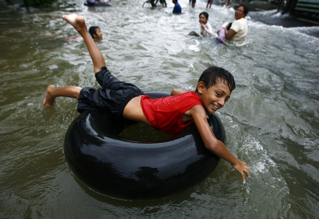 A boy plays on a flooded street in central Bago township, around 100 km north of Yangon