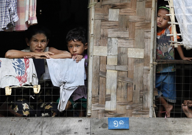A mother holds her child as they look out from their house on a flooded street in central Bago township