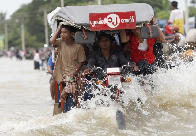 People ride on a vehicle on a flooded street in central Bago township, around 100 km (62 miles) north of Yangon
