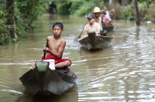 People travel by boats on a flooded street in central Bago township, around 100 km north of Yangon