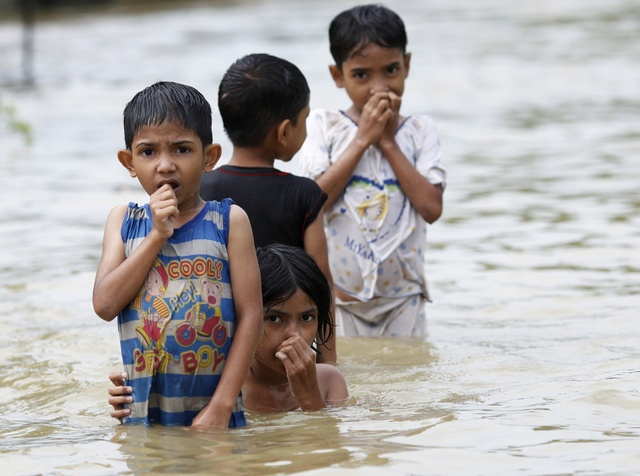 Children play on a flooded street in central Bago township, around 100 km (62 miles) north of Yangon