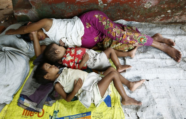 A pregnant mother and her children sleep at a monastery, which serves as a temporary shelter for flood victims in Bago township