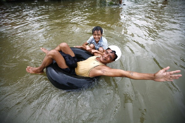 A man and his daughter play on a flooded street in central Bago township, around 100 km north of Yangon