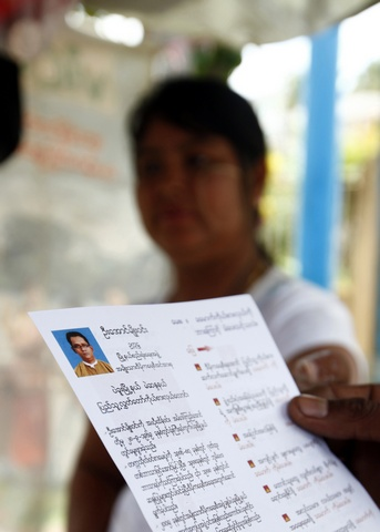 Members of the National Democratic Force hand out flyers as they campaign for votes for Myanmar's upcoming elections, in Bago