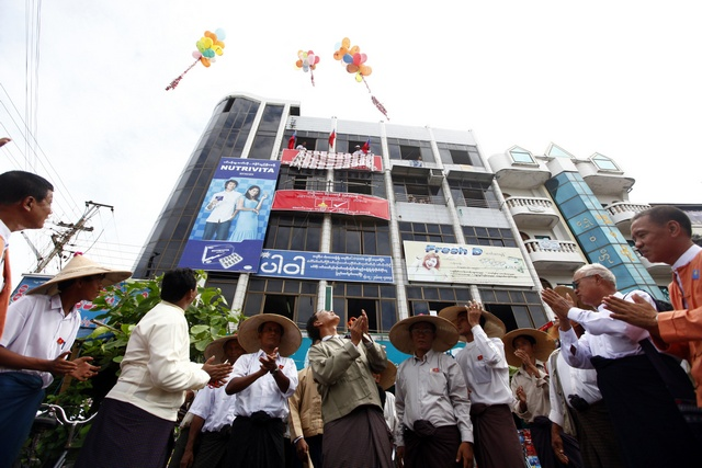 Members of the National Democratic Force party applaud as they watch released balloons at the opening ceremony of their division office in Bago