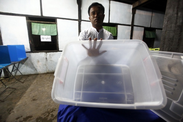 An official shows empty ballot box before the polling station is opened for voters in Sittwe