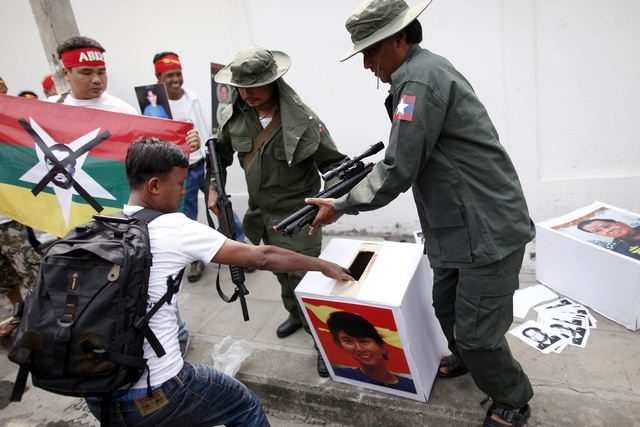 Pro-democracy activists dressed as soldiers prevent a fellow protester from casting his vote in a mock ballot box with the picture of Aung San Suu Kyi during a rally in Bangkok