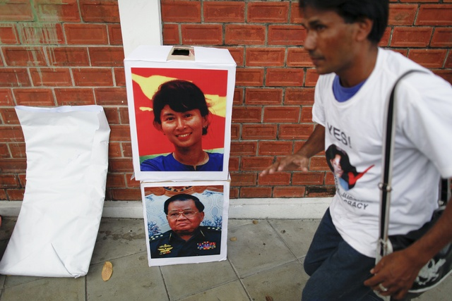 A pro-democracy activist runs past mock ballot boxes with pictures of Aung San Suu Kyi and Myanmar's junta's supremo Senior General Than Shwe during a protest in Bangkok