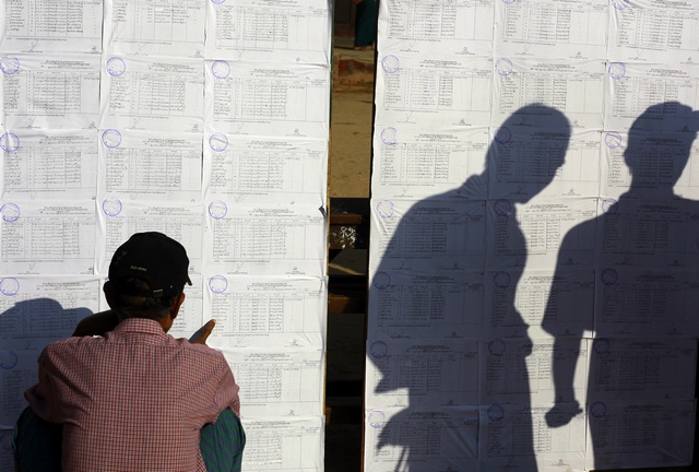 A man looks at the election material posted outside a polling station as others cast shadows in central Yangon