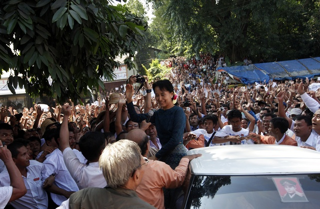 Aung San Suu Kyi waves to supporters gathered to hear her speech outside the headquarters of her National League for Democracy party in Yangon