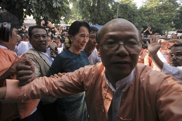 Aung San Suu Kyi makes her way through the crowd of supporters gathered outside the headquarters of her National League for Democracy party in Yangon