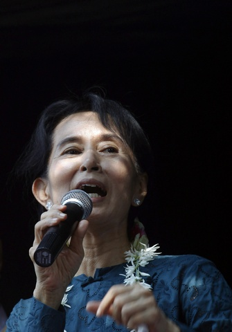 Aung San Suu Kyi addresses supporters gathered outside the headquarters of her National League for Democracy party in Yangon