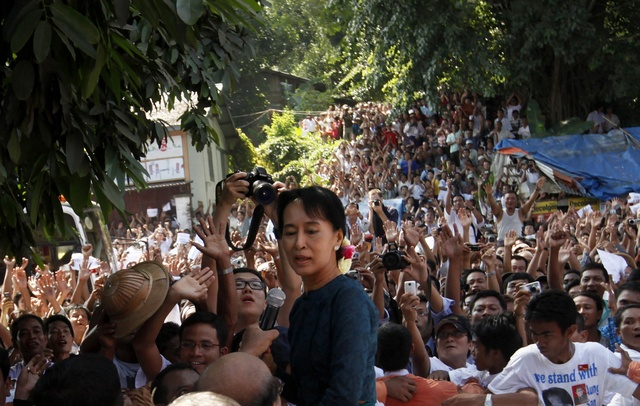 Aung San Suu Kyi stands among supporters gathered to hear her speech outside the headquarters of her National League for Democracy party in Yangon