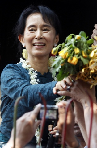 Aung San Suu Kyi receives flowers before addressing supporters gathered outside the headquarters of her National League for Democracy party in Yangon