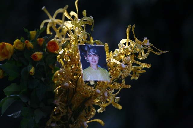 A photo of Aung San Suu Kyi is attached to flowers ready for her as she arrives to address supporters at the headquarters of her National League for Democracy party in Yangon