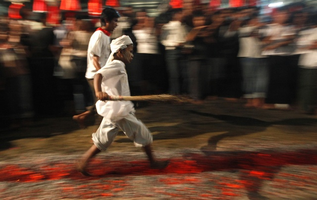A Shi'ite Muslim boy walks on fire at a ceremony during the Ashura festival at a mosque in central Yangon