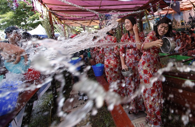 Ethnic Rakhine girls play with water as they celebrate Thingyan, Myanmar's new year water festival, in central Yangon