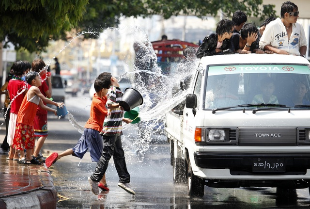Children throw water at vehicles while celebrating Thingyan, Myanmar's new year water festival, in central Yangon