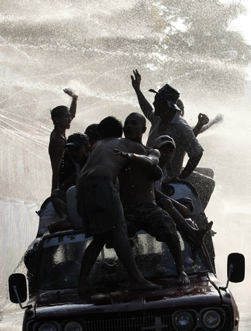 Locals riding a jeep get sprayed with water while celebrating Thingyan, Myanmar's new year water festival, in central Yangon