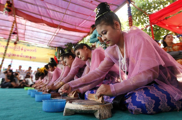 Girls participate in the Thanakha grinding competition during the Thingyan festival in Yangon