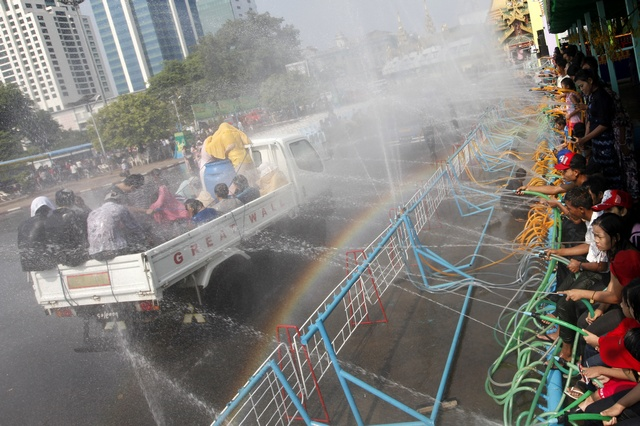 Locals riding vehicles get sprayed with water while celebrating Thingyan, Myanmar's new year water festival, in central Yangon