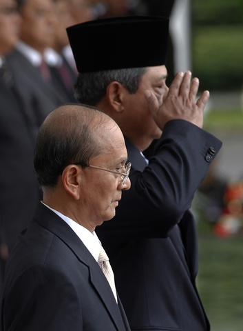 Myanmar Prime Minister Thein Sein accompanied by Indonesian President Susilo Bambang Yudhoyono stand for the national anthem during a welcoming ceremony at the Merdeka Palace in Jakarta