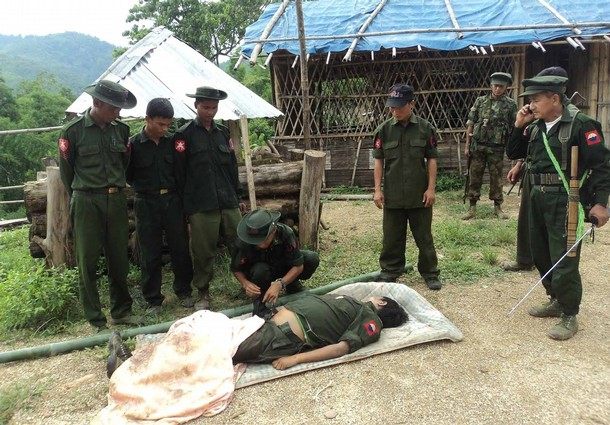 Kachin soldiers gather around the body of a comrade at an undisclosed location near the border with China