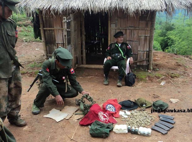Kachin soldiers gather around what they claim is ammunition captured in fighting with Myanmar government troops