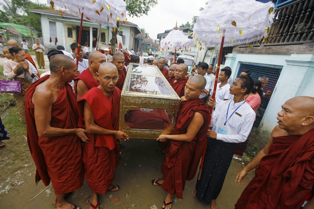 Buddhist monks carry the body of a respected monk at Nyein Chan Yae monastery in Yangon