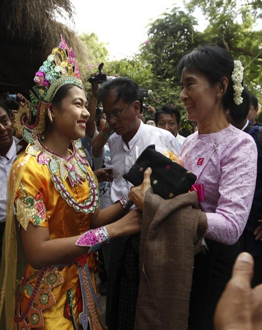 A hotel staff dressed as an ancient princess presents flowers to Myanmar's pro-democracy leader Aung San Suu Kyi in Bagan