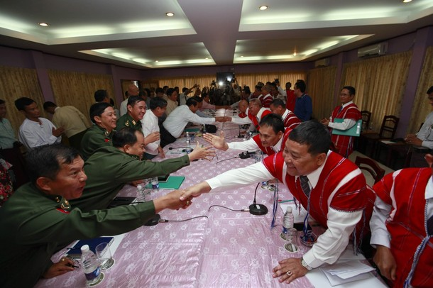 Representatives from Myanmar's government and KNU shake hands during peace talks at Hotel Zwekabin in Pa-an
