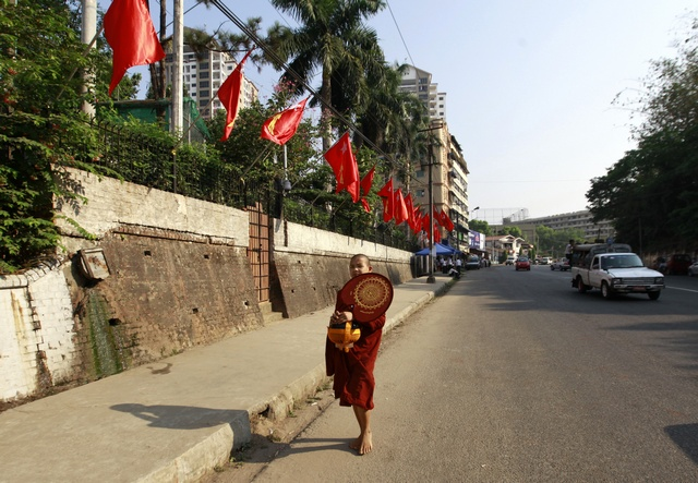 A Buddhist novice monk walks in front of the National League for Democracy party's (NLD) congress hall as he collects alums in Yangon